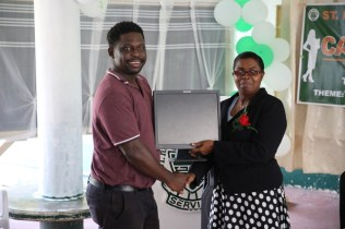 Principal of St Rose's High School, Paula Hamilton receives one of the computers from a representative of the Guyana Revenue Authority (GRA).