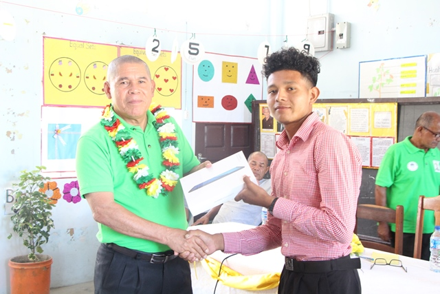 Minister of Social Cohesion Hon. Dr. George Norton presents an electronic tablet to one of the teachers of Capoey Primary School