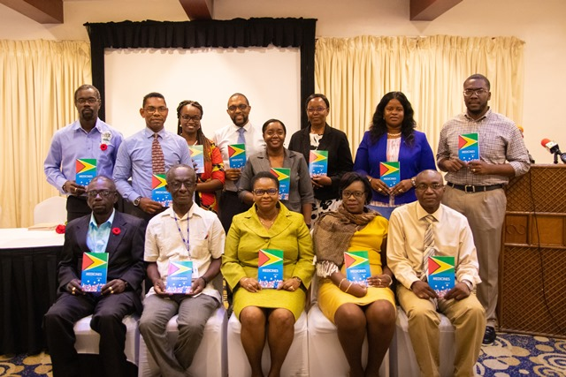 Directors and programme heads of the Ministry of Public Health and GPHC along with Minister Hon. Volda Lawrence poses with copies of the new GNMP that has been launched.