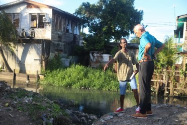 Minister of Communities, Hon. Ronald Bulkan having a firsthand look at the drainage situation in Alexander Village along with a resident of the community.