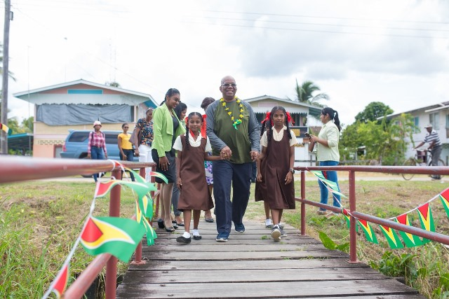 Minister of Finance, Hon. Winston Jordan is welcome by two students Success Primary School to Leguan