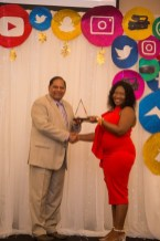 Vanessa Brathwaite, a Journalist from the Guyana Chronicle, receiving the overall winner plaque from Prime Minister, Hon. Moses Nagamootoo.
