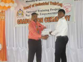 A graduate receiving his certificate from Charles Ogle, Chief Labour, Occupational Safety and Health Officer at the Ministry of Social Protection