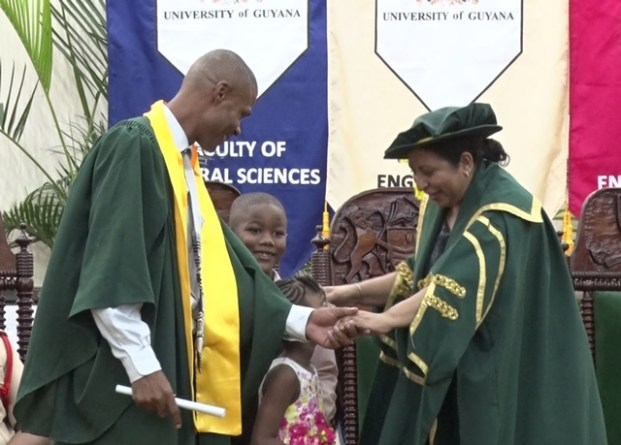 IDCE graduate Orvis Anthony Cox and his two children share a moment with Deputy Vice Chancellor of PACE Dr. Paloma Martin after receiving his certificate.