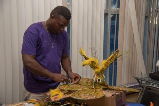 One of the local designers engrossed in creating his piece during the Guyana Together' - Mashramani Design Workshop