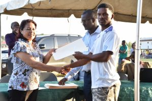 Minister of State, Dawn Hastings-Williams hands over an agreement of sale to one of the residents