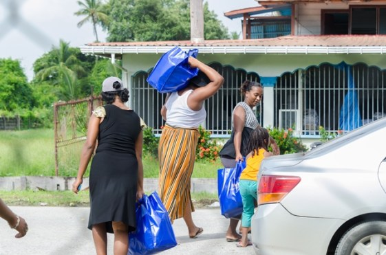 Some Plastic City residents returning to their homes with their hampers.