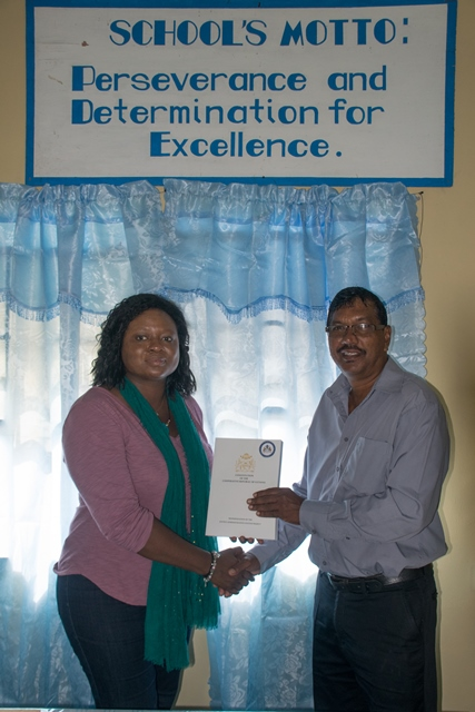 Coordinator of the Department of Governance at the Office of the Prime Minister (OPM), Tamara Khan, hands over a copy of the Constitution of Guyana to Headmaster of Wakapau Secondary School, Bulram Mohan.