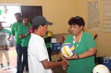 Minister of Social Protection, Hon. Amna Ally presents sport gear to a member of the community.