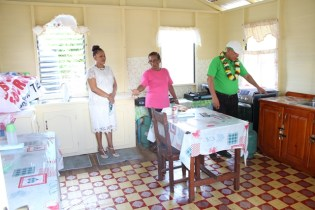 Mary Williams [pink shirt] Capoey Primary school's cook accompanied by a teacher shows Minister of Social Cohesion, Hon. Dr. George Norton around the kitchenette.