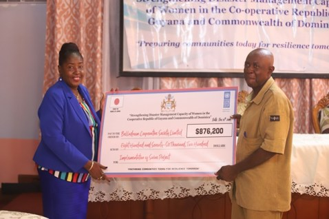 Hon. Valerie Adams-Yearwood presents a cheque to Julian David