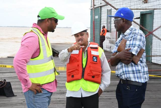 Minister within the Ministry of Public Infrastructure, Jaipaul Sharma in discussion contractor Sattrohan Maraj (left) Superintendent of Works, Transport and Harbours Department, Aubrey Walcott (right)