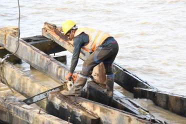 Workman sawing damaged beams as repairs continue on the affected portion of the Leguan Stelling