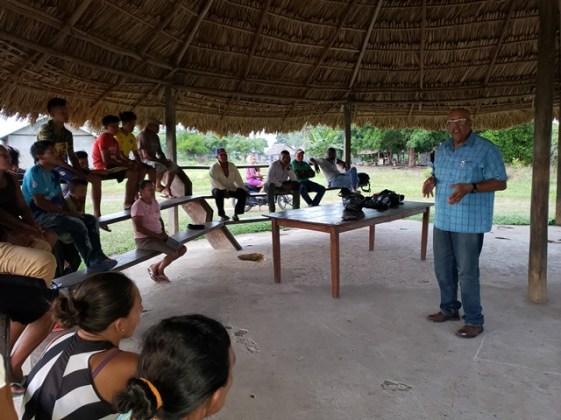 Dr. Van West-Charles addressing villagers in Crashwater.