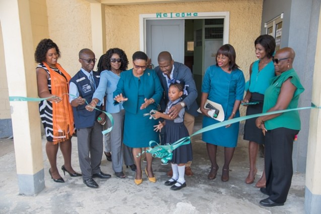 Little Trenyle Kanhai assists Minister of Public Health, the Hon. Volda Lawrence to cut the ribbon to the facility.