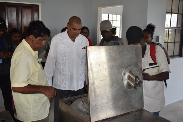 Minster of Business Haimraj Rajkumar being show how the equipment works by Supervisor, Lynn Halls (blue cap).