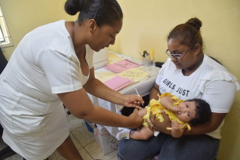 Midwife, Latoya Kellman administers a vaccine to one of her babies as the mother looks on