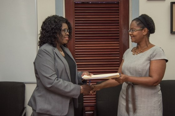 Ministry of Public Health's Permanent Secretary, Collette Adams shares signed agreement with Simone Sills, Executive Director of the National Coordinating Coalition of NGOs.