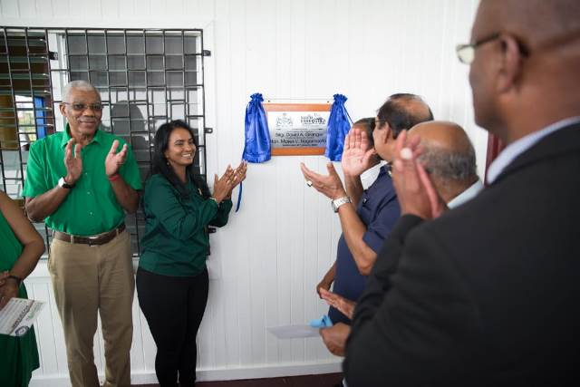 President David Granger Prime Minister Moses Nagamootoo and other officials applaud as former Deputy-Mayor of Bartica Nageswari Kamal Lochanprasad and a Region Two student unveil the plaque to commemorate the commissioning of Radio Essequibo.