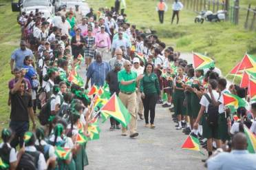 Region two school students greet President David Granger as he arrives to commission the radio station.