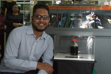 Shiv Outar, the Guyanese offshore technician who tested Guyana's first crude posing with the sample.