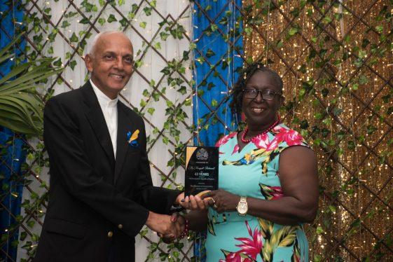 Longest serving member Ms. Margaret Richmond receives her award from Minister of Communities Ronald Bulkan