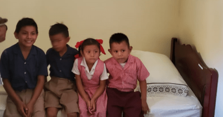 Students of the Nursery School seated on the new bed.