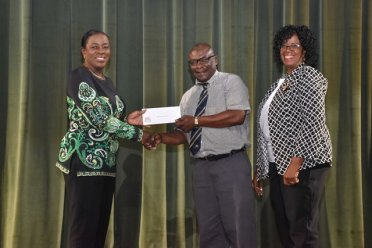 Banks DIH Ltd. Communications Manager, Troy Peters makes a presentation to Minster of Education, Hon. Dr. Nicolette Henry (left) and Unit of Allied Arts Administrator, Lorraine Barker-King on behalf of Banks DIH Ltd.