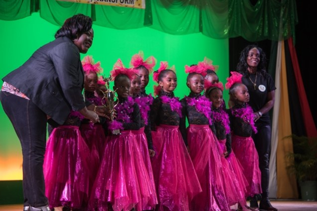 Westfield Prep Dancers (center) and Teacher (right) receive their award from a Ministry of Education Representative (left) for First place in the 5-7 Dance Category.