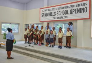 Headmistress Gem Bowman leads students and teacher in song during the commissioning of the Sand Hills Primary School