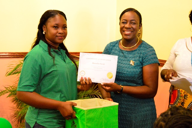 One of the graduates receiving their certificates and start-up kits.