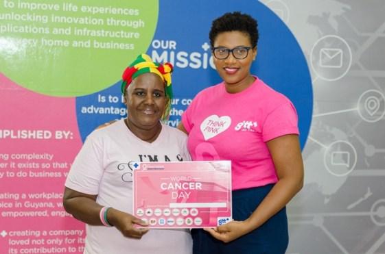 Anna De Morias, cancer patient receives a ceremonial voucher from Diana Gittens, Pinktober Coordinator, GTT+.