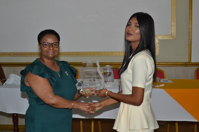 Minister of Public Health, Volda Lawrence hands over the award to the Valedictorian of the Community Health Worker batch, Schabana Harrichand.