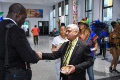 Minister within the Ministry of Public Infrastructure Hon. Jaipaul Sharma helps to welcome the arriving passengers