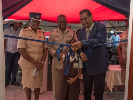 Grade 4 student of District Number 10 Nursery School, Neila Mohabir cuts ribbon to the recommissioned police outpost in the presence of [L-R] Minister of Public Security, Hon. Khemraj Ramjattan; Commissioner of Police, Leslie James; Superintendent Yonette Stephens.