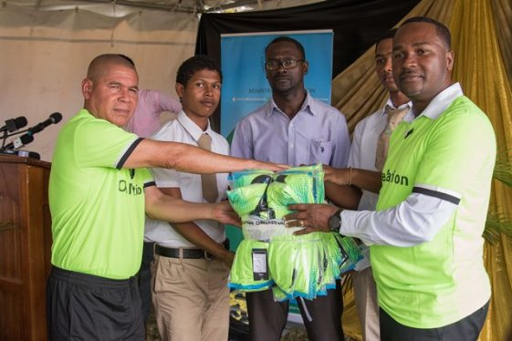 Minister of Social Cohesion Dr. George Norton and President of the Guyana Football Federation Wayne Forde handing over sports gear to Charlestown Secondary School.