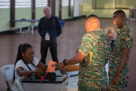 A member of the Guyana Defence Force casts his ballot as an observer from EU Elections Observer Mission looks on.