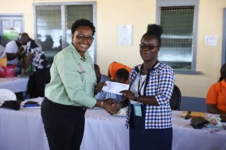 Minister within the Ministry of Communities Annette Ferguson handing over a letter of allocation to Andrea Cummings.