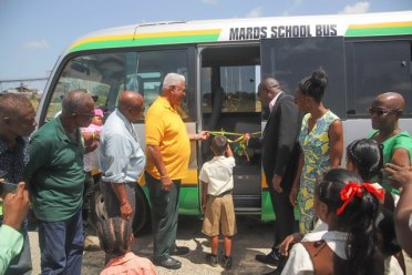A pupil of the Augsburg Primary School assisted Minister of Agriculture, the Hon. Noel Holder and Public Infrastructure Minister, the Hon. David Patterson with the cutting of ribbons to the $7.3M' MARDS school bus.