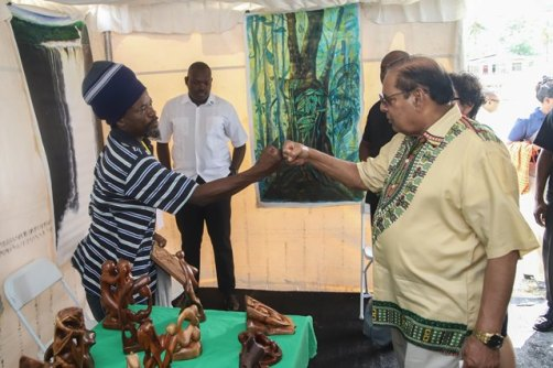 Prime Minister Hon. Moses Nagamootoo greeting a vendor 'Guyanese style'.