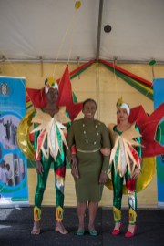 Minister of Education, Dr. the Hon. Nicolette Henry sharing a light moment with two students displaying their costume.
