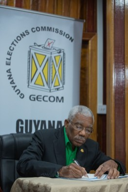 HE President David Granger signs GECOM's Code of Conduct.