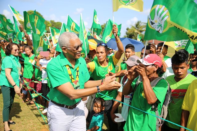 HE President David Granger greets supporters as he makes him way to the rally at Mabaruma.