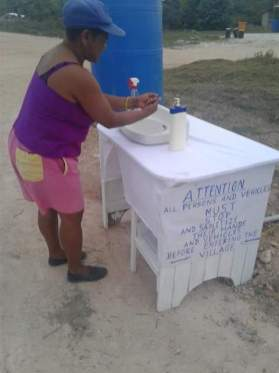 A resident of Coomacka washing her hands at the sanitisation station