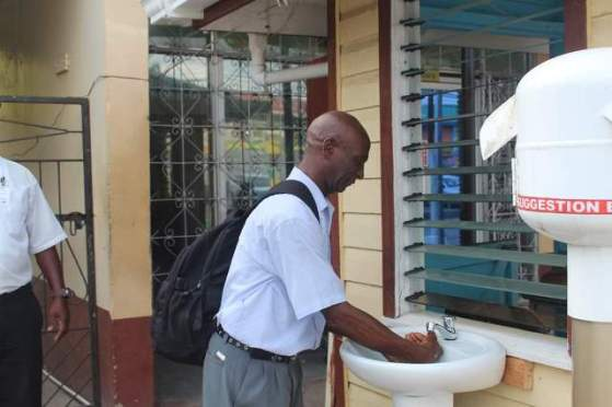 Regional Vice Chairman Elroy Adolph practicing handwashing at the RDC's sanitation block