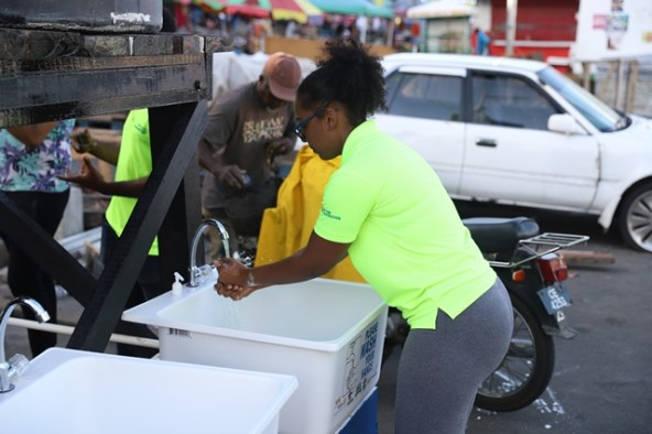 A member of the Rotary Club of Georgetown Central demonstrating how to use the handwashing station.