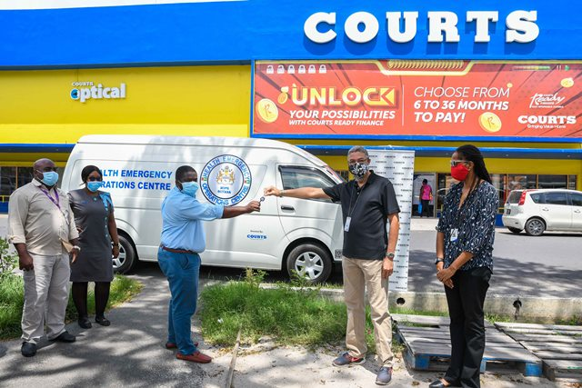 Managing Director of Courts Guyana, Clyde De Haas hands over the keys to Dr. Leston Payne, Deputy Director of the Health Emergency Operations Centre in the presence of staff members.