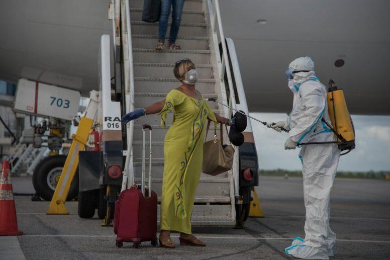 Returning Guyanese nationals being sanitised upon entry at CJIA