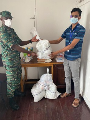 Director-General of CDC, Lieutenant-Colonel Kester Craig receives the donation from IOM's Project Assistant Mr. Javiel Singh.