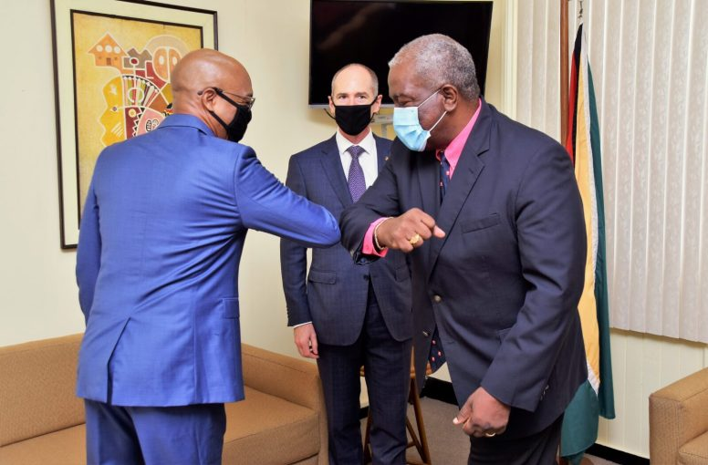 Prime Minister Brigadier Mark Phillips (right), greets Senior Director of Government Relations of Esso Exploration and Production, Guyana Limited, (ExxonMobil) Mr. Marcus Tripp (left), as Country Director, Mr. Alistair Routledge looks on
